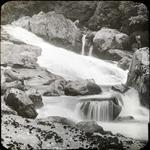 Two men beside a waterfall